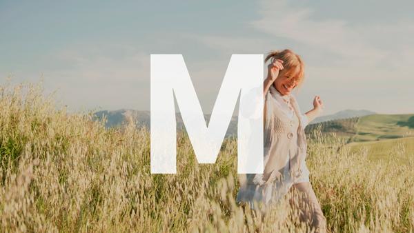Glückliche Frau die durch ein Feld springt