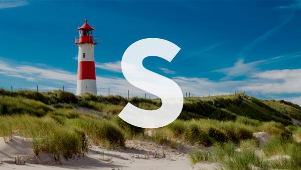 Leuchtturm im Feld am Strand bei strahlend blauem Himmel