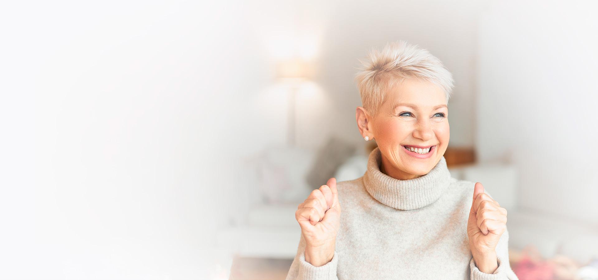 Glückliche ältere Frau zuhause im Wohnzimmer die sich ganz besonders freut