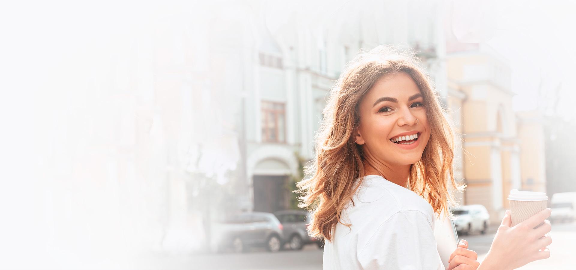 Junge lächelnde Frau mit Kaffee in der Hand in einem sonnigen Wohngebiet